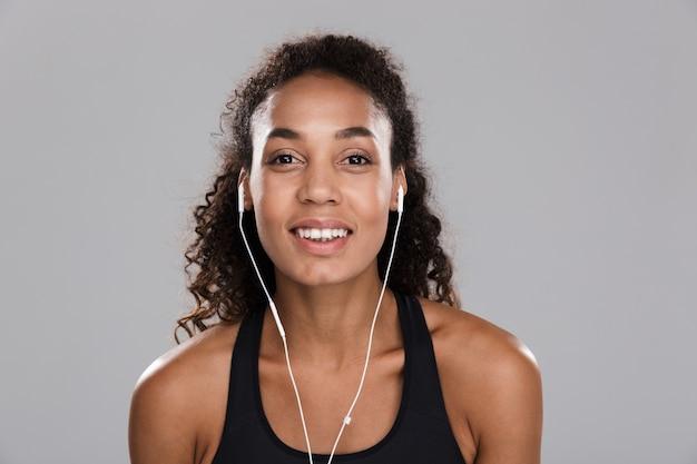 Retrato de una joven deportista alegre afroamericana aislada sobre fondo gris, escuchando música con auriculares