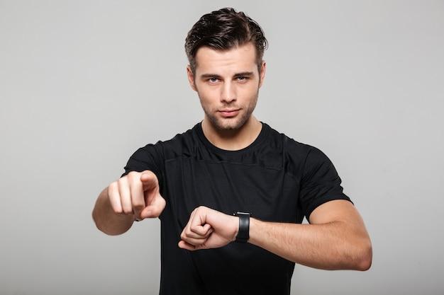 Retrato de un joven deportista confiado que muestra su reloj de pulsera