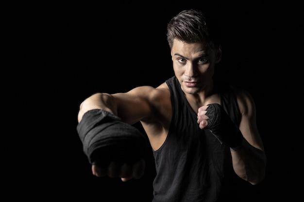 Retrato de joven deportista en envolturas de boxeo posando en postura de boxeo