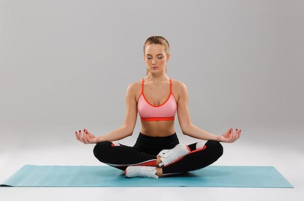Retrato de una joven deportista en forma meditando