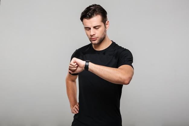Retrato de un joven deportista mirando su reloj de pulsera