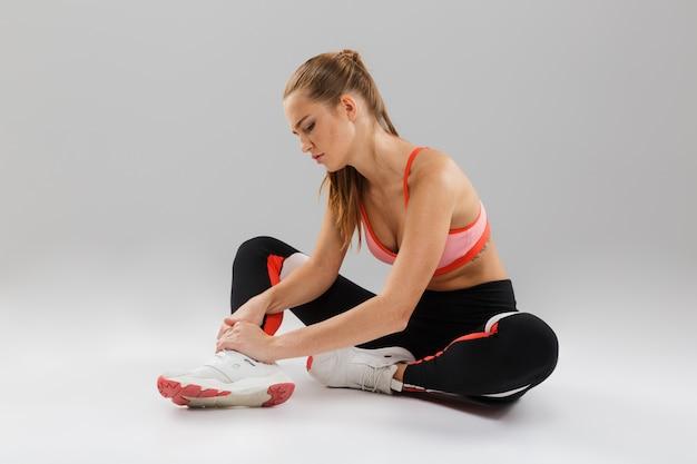 Retrato de una joven deportista que sufre de dolor en el tobillo