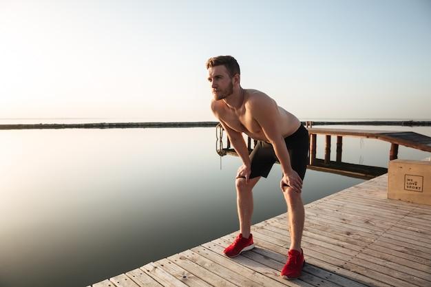Retrato de un joven deportista sano descansando después de correr al aire libre