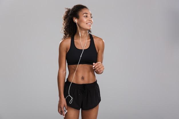 Retrato de una joven deportista sonriente afroamericana aislada sobre fondo gris, escuchando música con auriculares