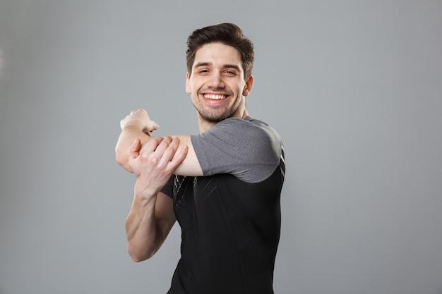 Retrato de un joven deportista sonriente calentando
