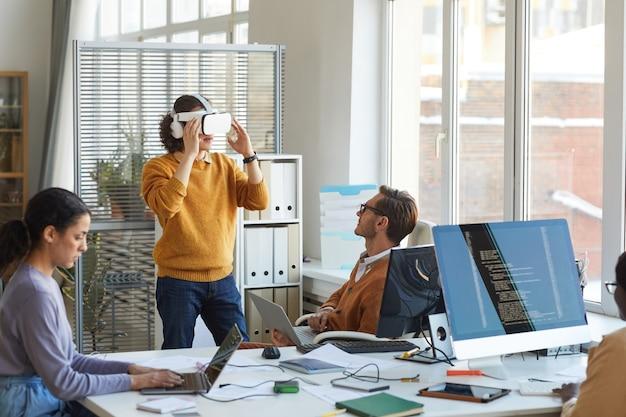 Retrato de joven desarrollador de ti probando equipo de realidad virtual mientras trabaja con el equipo en el estudio de producción de software, espacio de copia