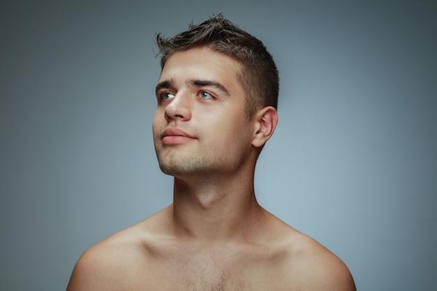 Retrato de joven descamisado aislado en estudio gris