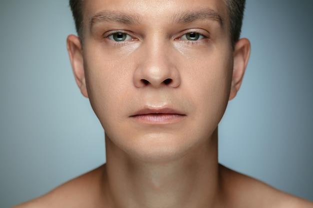Retrato de joven descamisado aislado en la pared gris. modelo masculino caucásico sano que mira la cámara y que presenta. concepto de salud y belleza de los hombres, cuidado personal, cuidado del cuerpo y de la piel.