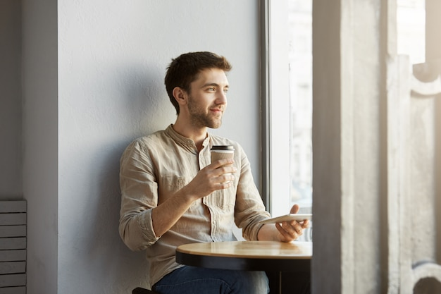 Retrato de joven diseñador masculino independiente en perspectiva sentado en la cafetería, mirando a un lado satisfecho con su nuevo proyecto.