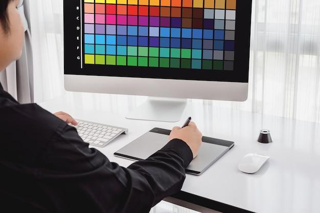 Retrato de joven diseñador masculino, trabajo independiente con colores en casa