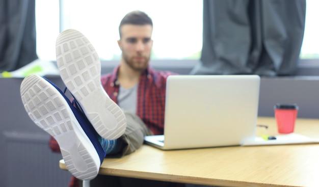 Retrato de un joven diseñador muy relajado que se inclina hacia atrás en su escritorio y pone los pies sobre su escritorio en la oficina.