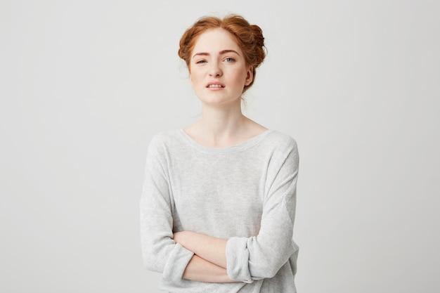 Retrato de joven disgustada jengibre chica con los brazos cruzados.
