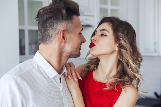 Retrato de joven divertida besa a su hombre guapo