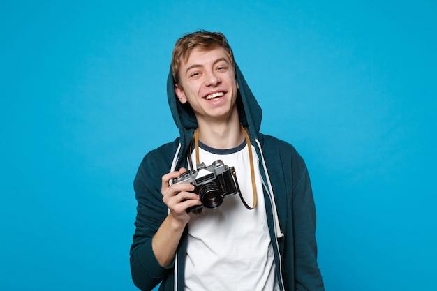 Retrato de joven divertido alegre en ropa casual sosteniendo en las manos cámara de fotos vintage retro aislada en la pared azul. personas sinceras emociones, concepto de estilo de vida.