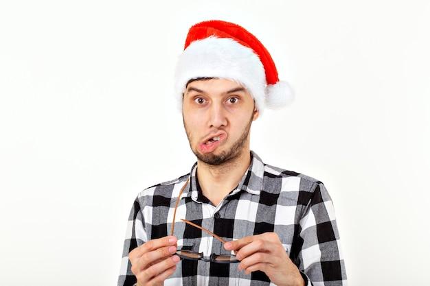Retrato de un joven divertido con sombrero y barba de santa claus. navidad.
