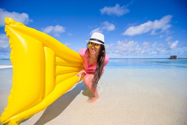 Retrato de joven divirtiéndose con colchón de aire en la piscina