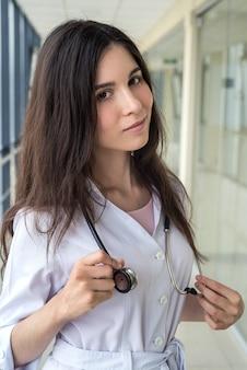 Retrato de joven doctora en un instituto médico con estetoscopio. espacio publicitario