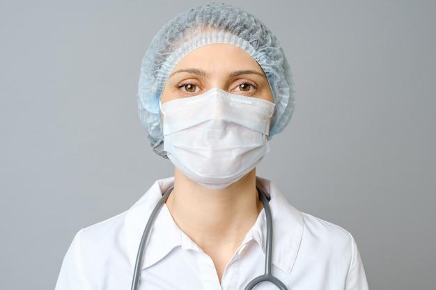 Retrato de joven doctora en máscara médica protectora en su rostro y gorra en la cabeza. aislado en la pared gris
