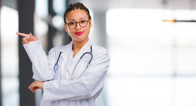 Retrato de una joven doctora negra apuntando hacia un lado, sonriendo sorprendida presentando algo, natural y casual
