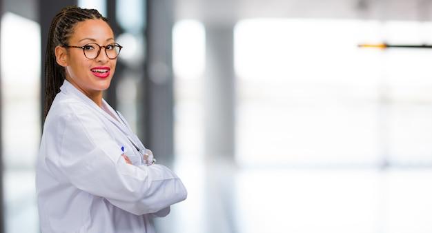 Retrato de una joven doctora negra que cruza sus brazos, sonriente y feliz, confiada y amigable