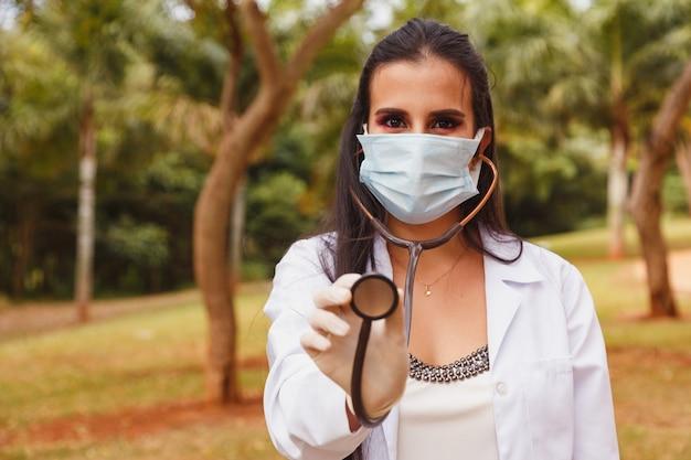 Retrato de joven doctora o enfermera con bata de laboratorio y estetoscopio fuera
