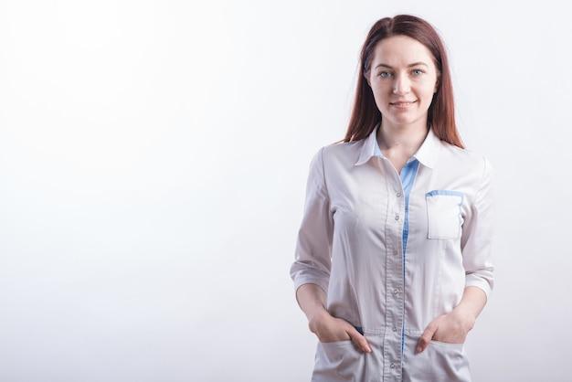 Retrato de una joven doctora con un uniforme blanco en el estudio sobre un fondo blanco con copyspace