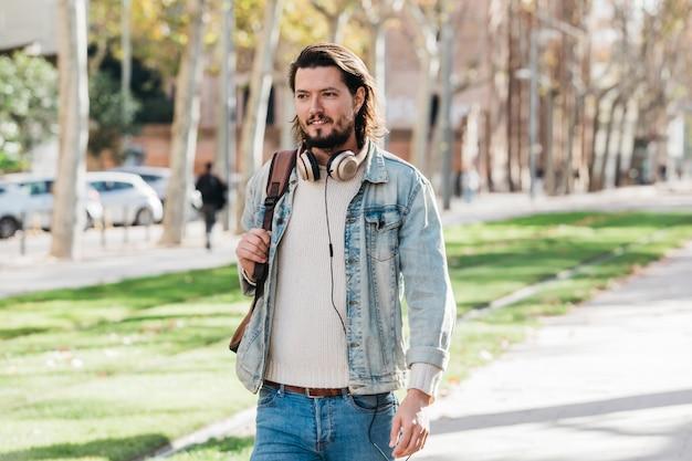Retrato de un joven elegante con auriculares alrededor de su cuello caminando en el parque