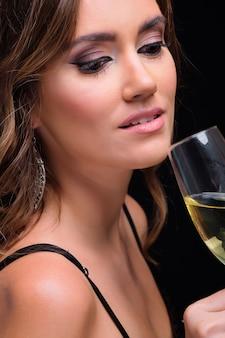 Retrato de joven elegante bebiendo champán contra negro