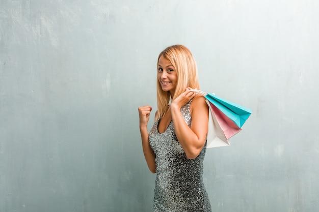 Retrato de joven elegante mujer rubia muy feliz y emocionada, levantando los brazos