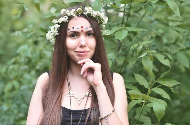 Retrato de una joven emocional con una guirnalda floral en la cabeza y adornos brillantes en la frente. linda morena posando en un hermoso bosque floreciente durante el día en un buen día
