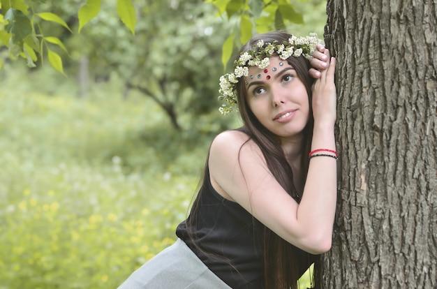 Retrato de una joven emocional con una guirnalda floral en la cabeza y adornos brillantes en la frente