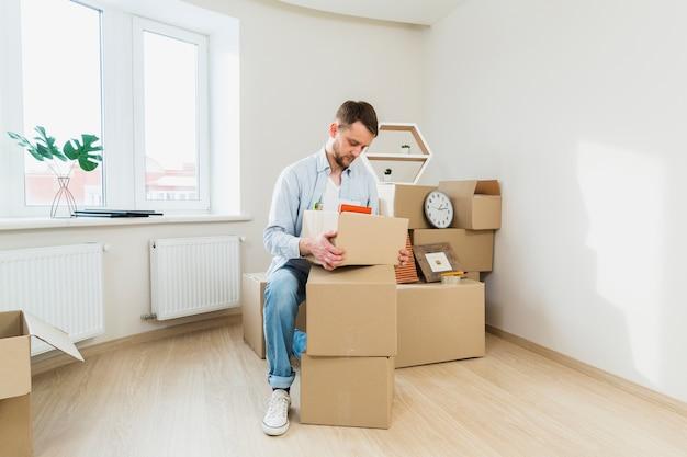 Retrato de un joven empacando las cajas de cartón en casa.