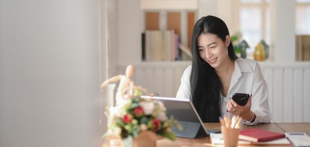 Retrato de joven empresaria adorable trabajando en su proyecto en la oficina moderna