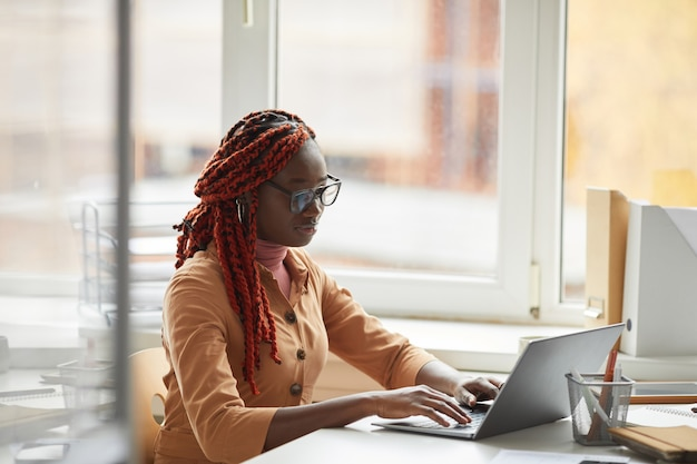 Retrato de joven empresaria afroamericana usando laptop mientras está sentado en el escritorio junto a la ventana y disfruta del trabajo en la oficina, espacio de copia