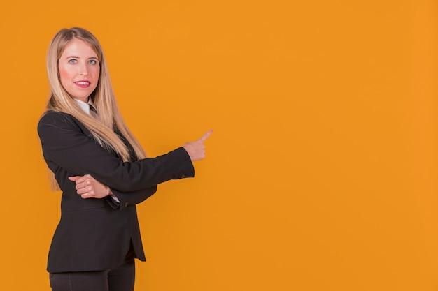 Retrato de una joven empresaria apuntando su dedo contra un fondo naranja