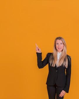 Retrato de una joven empresaria apuntando su dedo contra un telón de fondo naranja