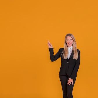 Retrato de una joven empresaria apuntando su dedo sobre un fondo naranja