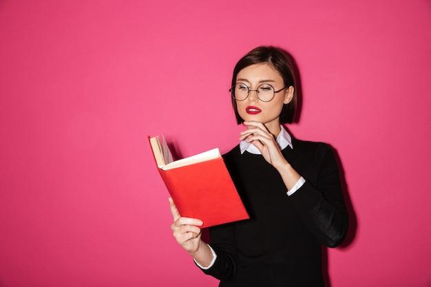 Retrato de una joven empresaria atractiva leyendo un libro