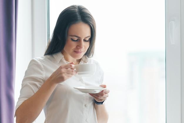 Retrato de joven empresaria en camisa blanca con taza de café