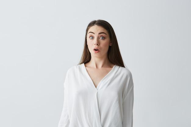 Retrato de joven empresaria hermosa sorprendida con la boca abierta.