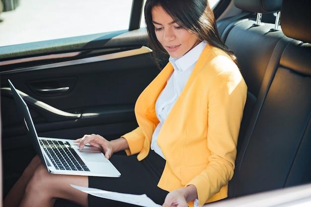 Retrato de una joven empresaria con laptop en el asiento trasero del coche
