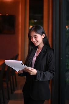 Retrato de joven empresaria leyendo el documento en la oficina.