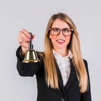 Retrato de una joven empresaria sosteniendo la campana de oro sobre fondo gris