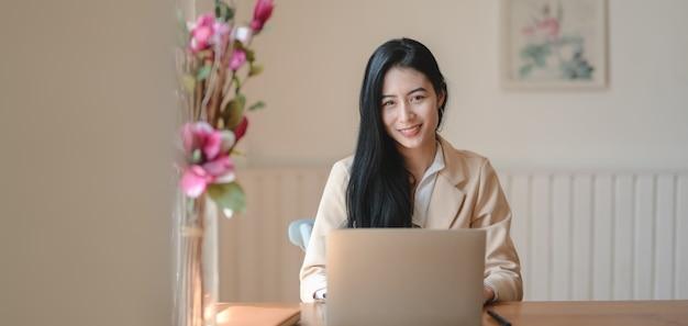 Retrato de joven empresaria trabajando en su proyecto con computadora portátil mientras sonríe a la cámara