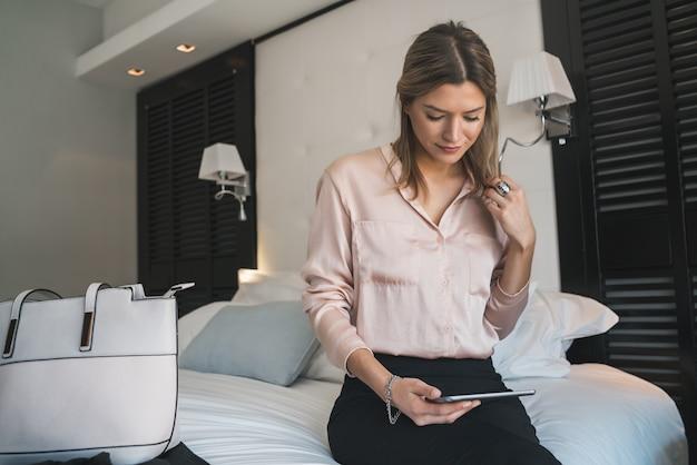 Retrato de joven empresaria trabajando en su tableta digital en la habitación del hotel.