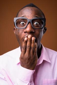 Retrato de joven empresario africano contra la pared marrón