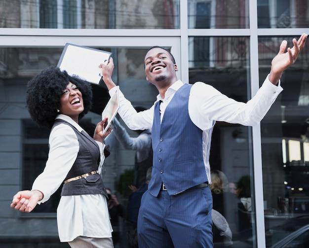 Retrato de un joven empresario africano y empresaria disfrutando del éxito
