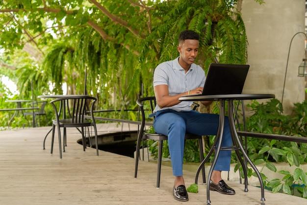 Retrato de joven empresario africano vistiendo ropa casual y sentado en la cafetería mientras usa una computadora portátil y distanciamiento social