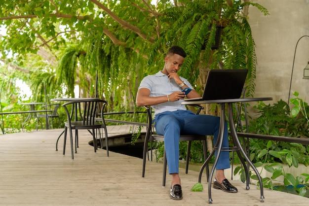 Retrato de joven empresario africano vistiendo ropa casual y sentado en la cafetería mientras usa una computadora portátil y un teléfono mientras que el distanciamiento social