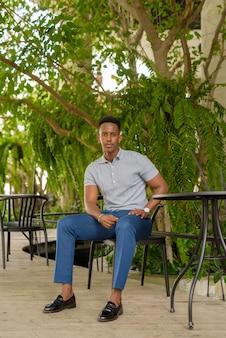 Retrato de joven empresario africano vistiendo ropa casual y sentado en la cafetería.